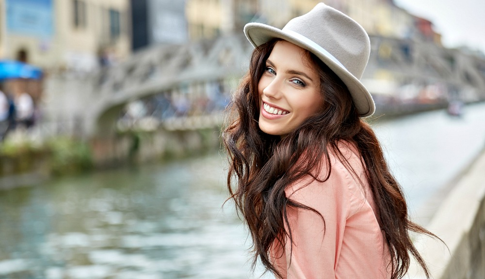Smiling girl wearing summer shirt at riverside